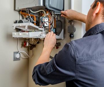 Idraulico manutentore effettua la revisione della caldaia murale a gas